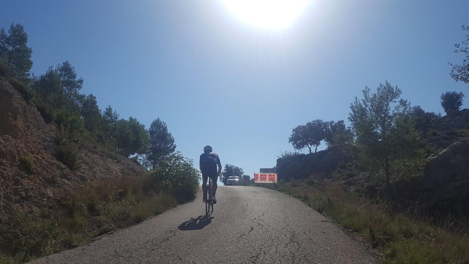 Cyclist climbing mountain under the sun