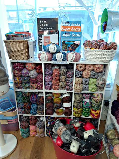 A photo showing a display of sock yarns.  There is a storage unit with nine square sections, each full of balls of yarn.  On top of the unit is a basket on the left containing knitting patterns, balls of yarn in the centre, a stand containing Winwick Mum Super Socks and More Super Socks books and a basket on the right containing balls of sock yarn.