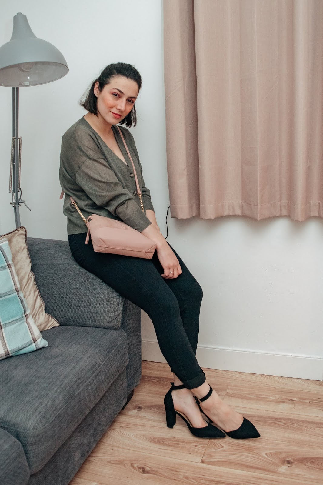 Sitting on a grey sofa wearing a boxy khaki cardigan, black jeans and black pointed heels.