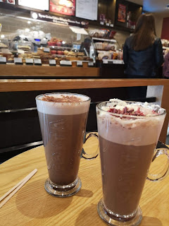 A picture of two cylindrical clear glasses with costa engraved into them filled with brown ;oxide and topped with white cream, one with red sauce and glitter on top and the other with small bits of light brown wafer on a light brown rectangular table on a bright background