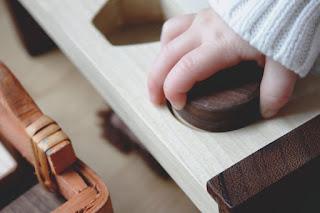 Main d'enfant qui manipule un jeu Montessori