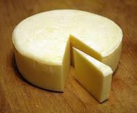 Bir dilimi kesilmiş yuvarlak kaşkaval peyniri