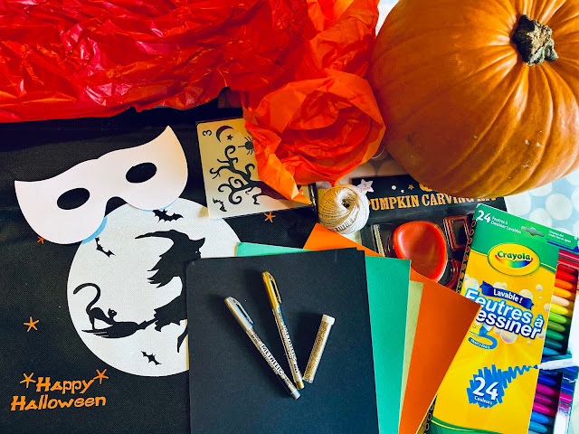 Various Halloween themed craft items including card in black, green and orange, felt tip pens, silver and gold metalic pens, a pumpkin carving kit and string