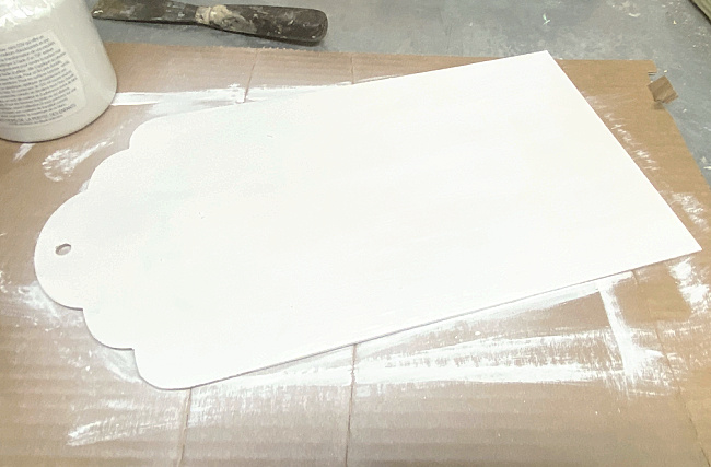white painted tag shaped piece