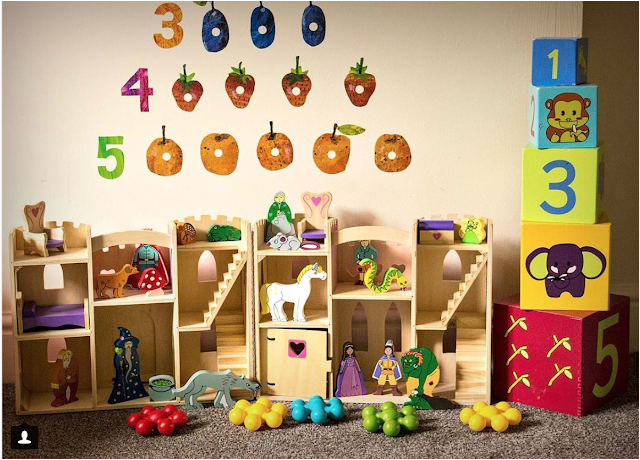 A playroom with stickers on the wall, a wooden play castle and stacking blocks