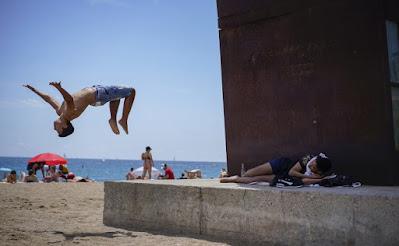 Seorang anak laki-laki melakukan back flip di pantai Barcelona, Spanyol, Minggu, 27 Juni 2021. Hampir setahun setelah masker wajah menjadi wajib di dalam dan luar ruangan di Spanyol, orang-orang mulai Sabtu tidak lagi diharuskan memakainya di luar selama mereka bisa tinggal setidaknya 1,5 meter (5 kaki) terpisah. AP