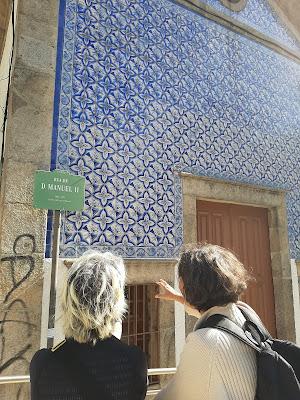 Duas mulheres observando uma parede de azulejos no Porto