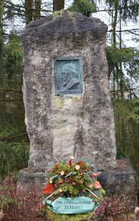 Der Dolomitstein mit Relief wird immer als Gedenkstelle benutzt. Kranzniederlegung.