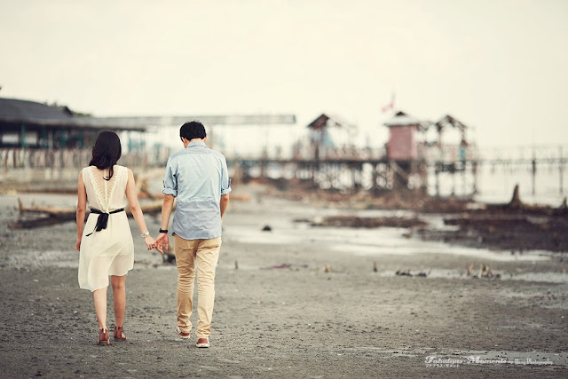 back of couple walking sand