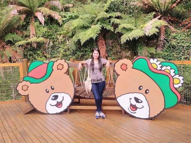 mulher posando para foto no meio de dois banners com carinhas de ursinhos