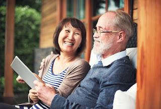 An older couple smiling and sitting on a front porch looking at a tablet in Belleville, ON