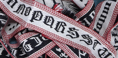 A photograph of a jumbled heap of black, red and white tablet woven bands featuring different letters