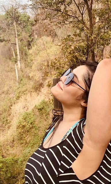 mulher de perfil segurando o cabelo com o braço direitp em uma ponte