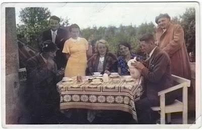 Kaffeetafel mit Damen und Herren. Alte Frisuren und Kleider, Bank aus weißgestrichenem Holz, Stofftischdecke. (Kaffeetafel 1927)