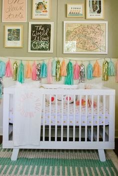 nursery with gold, aqua and pink detail and tassel garland