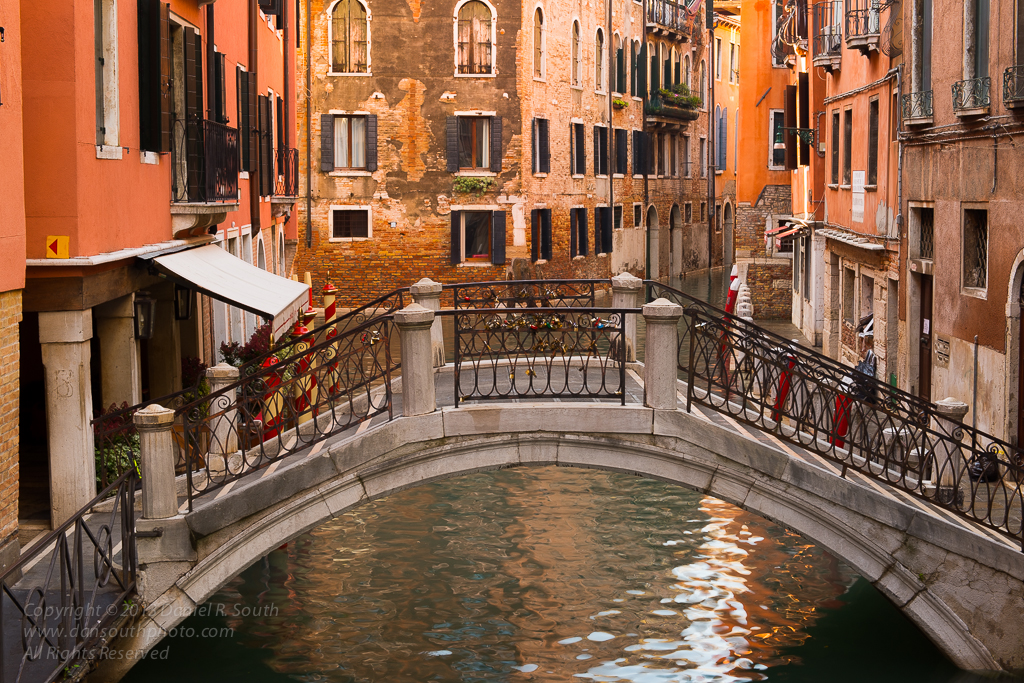 a photo of a bridge over a quiet canal in venice by daniel south