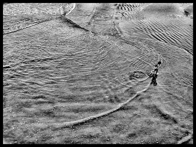 Niño scorriendo saliendo del mar fuera de cuadro.