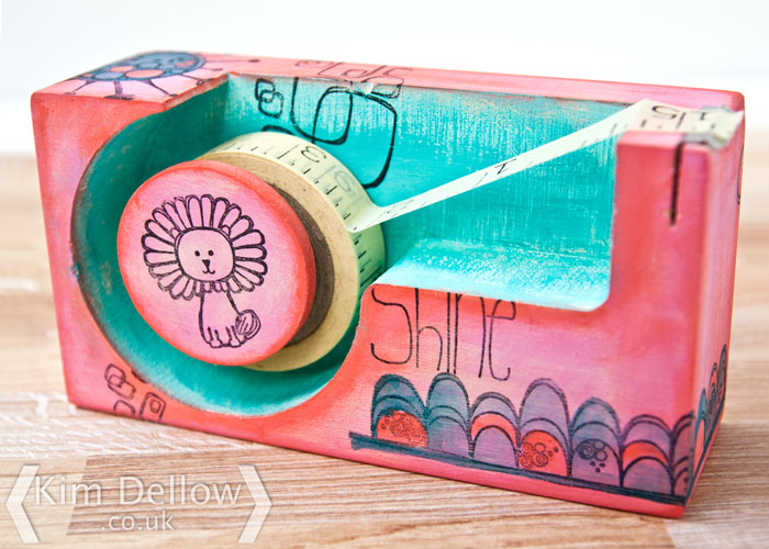A decorated tape dispenser by Kim Dellow using stamps and paints