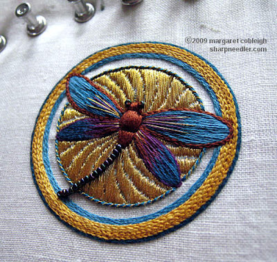 Completed embroidered dragonfly on top of underside couching in gold. This version of the dragonfly is in browns and blues with beads along the tail and touches of gold on the wings.