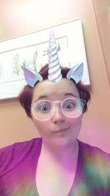 me in a reddish-purpleish shirt in front of a brown clinic wall with boring art behind me; a snapchat filter has turned me into a unicorn with a white horn, white ears, and white glasses, as well as adding a bit of rainbow to various parts of the photo