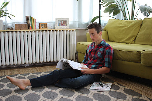 Teen reading on living room floor