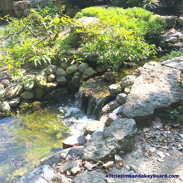 A waterfall tranquilly flows in the Japanese garden.