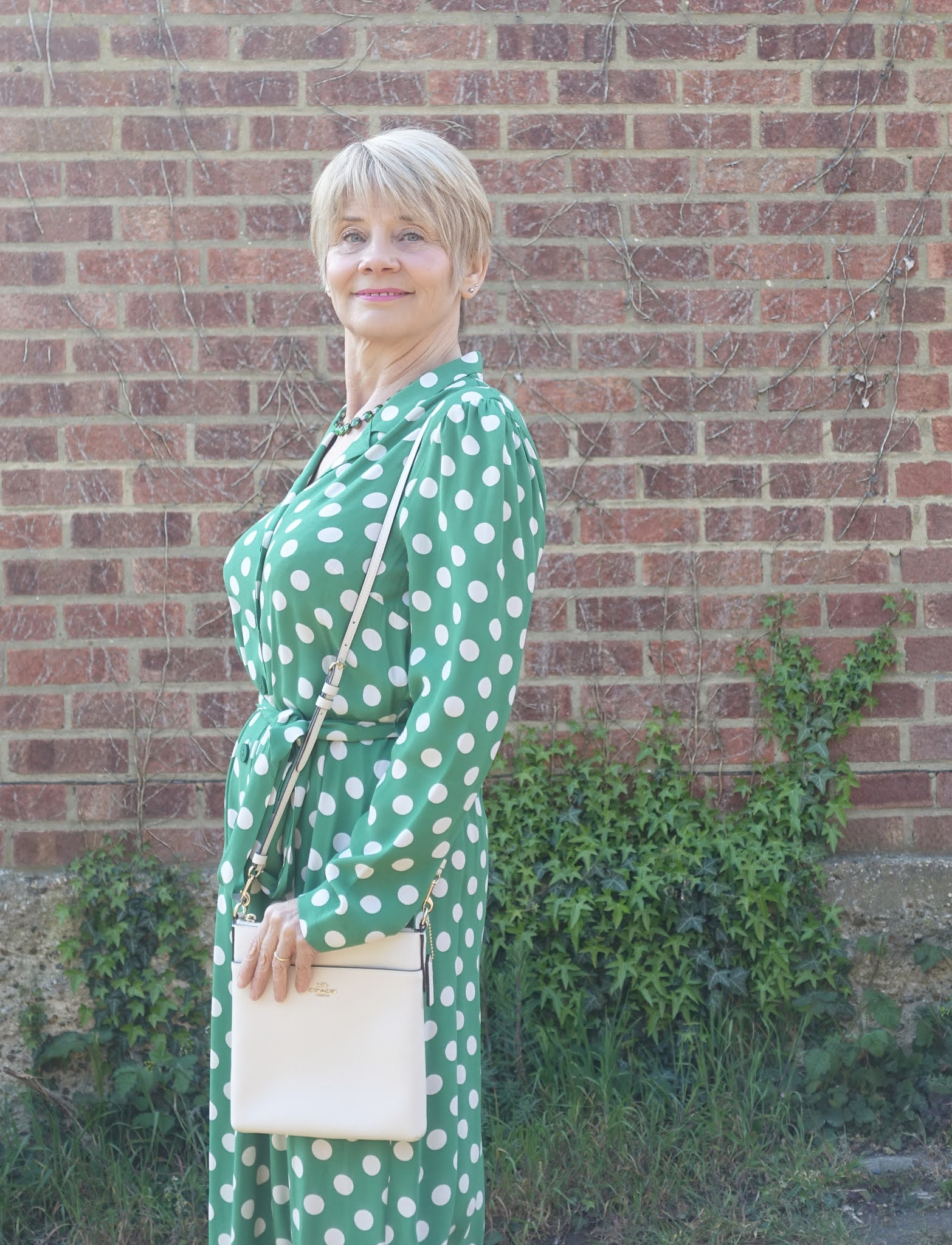 A green shirt waister dress with polka dots and belt from M&S worn by over-50s blogger Gail Hanlon and accessorized with green sequin T bar shoes from Irregular Choice
