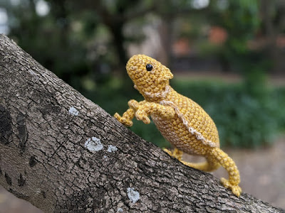 Finished crochet bearded dragon crawling up a tree