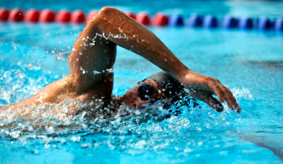 Picture of a mans swimming freestyle in the pool. Four Causes Of Shoulder Pain and Swimming Injury. Four Causes Of Shoulder Pain and Swimming Injury