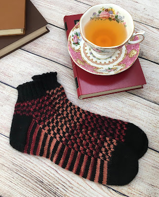 Socks knitted with prism pattern laying next to 3 books and a cup of tea