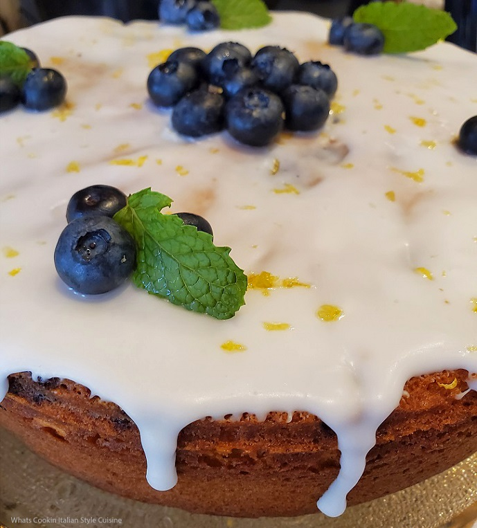 this is a blueberry cake mix cake with blueberries and mint on top of lemon frosting drizzled down the sides of the cake along with fresh mint on top and grated lemon peel
