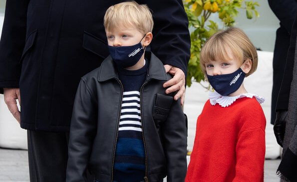 Princess Gabriella wore a red sweater. Princess Charlene wore a tropicalia toile de jouy opera coat from Christian Dior. Louis Vuitton boots