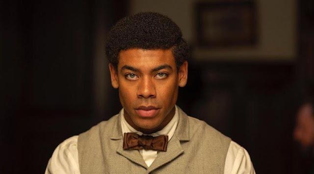 A black man stares at camera