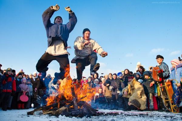 Jóvenes saltando por encima de la hoguera en el festival de Máslenitsa