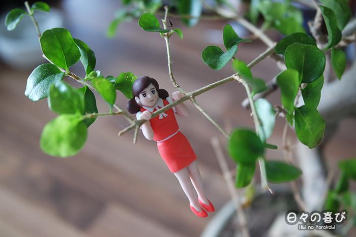 Fuchiko accrochée à la branche d'un bonsai