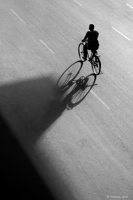 A Black and White Minimalist Photograph of a Man commuting to work on his Bicycle and a Big Shadow Triangle formed on the Street.
