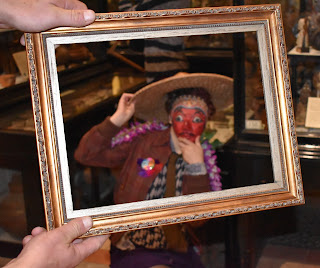 A framed portrait of young person standing next to a Pitt Rivers Museum case wearing a mask from Java and a hat from China