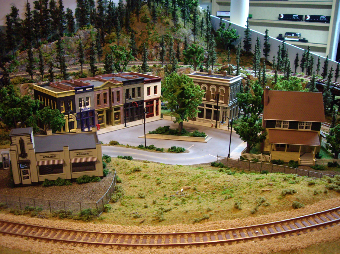 A downtown scene with several plastic model kits surrounding a circular road with a center median garden