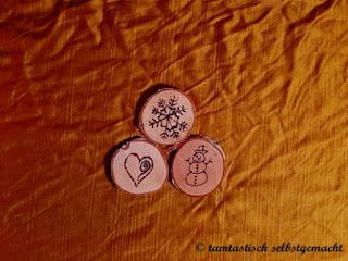3-kleine-mit-Brandmalerei-gestalte-Baumscheiben-mit-den-Motiven-Schneeflocke-Schneemann-Herz