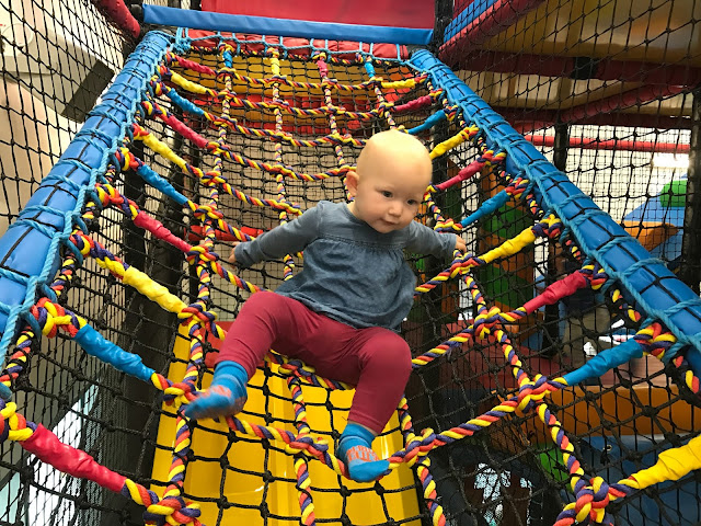 A 1 year old climbing down colourful rope netting