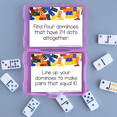 Photo of task cards in purple container with dominoes next to it.