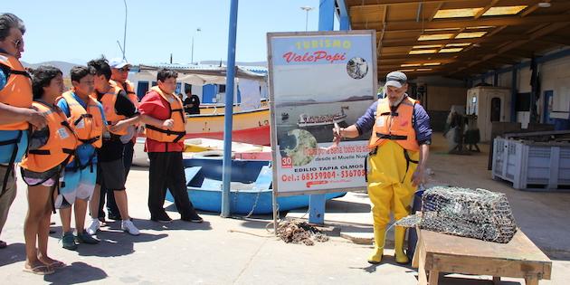 pescador instruye a turistas en pesca de jaiba