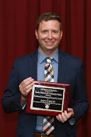 Dr. Bader smiles and holds his award plaque