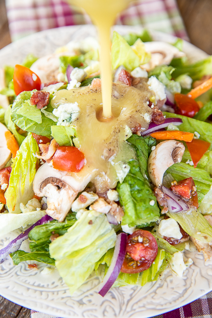 pouring dressing on top of a salad