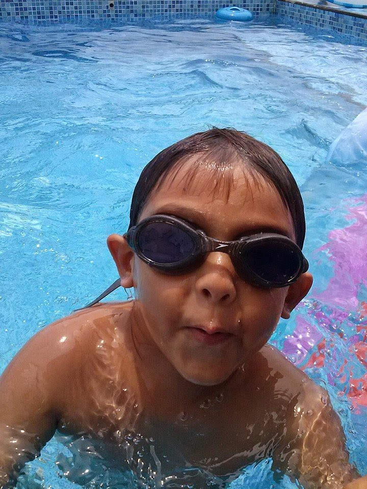Cool kid in swimming pool with goggles