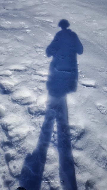 Persons shadow as they walk on a snow covered field. www.ruralmag.com