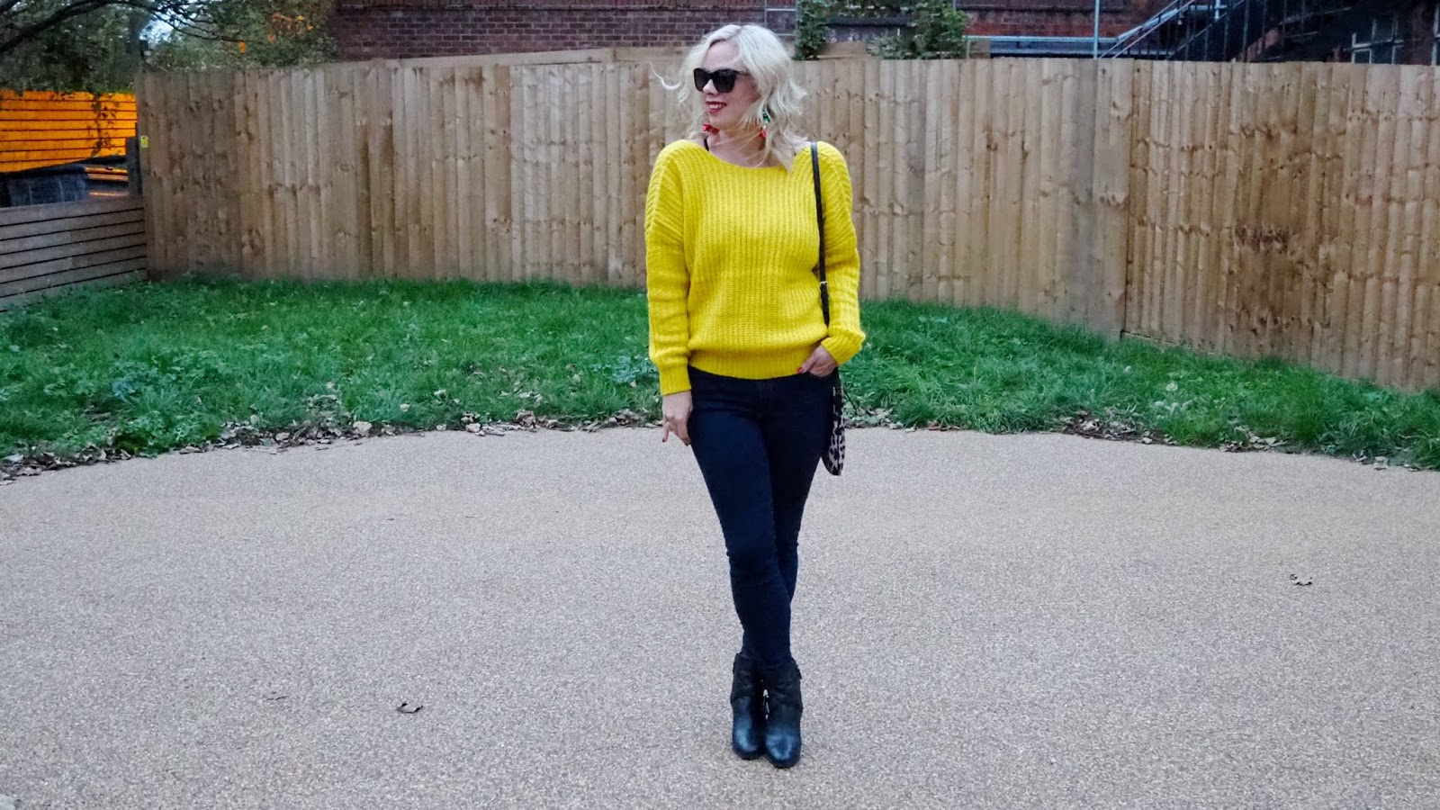 Yellow Sweater, dark rinse skinny jeans, black ankle boots, black sunglasses, red lipstick and leopard cross-body bag