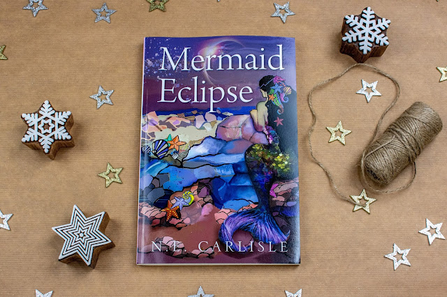 The Mermaid Eclipse book by N.E.Carlisle showing a painting of a mermaid on a beach.