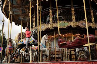 Little girl riding horses in the rotunda of Paris