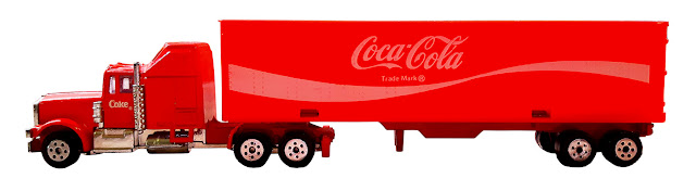 A small transport trailer toy with a plastic trailer and the Coca-Cola trademark, and a metal cab.